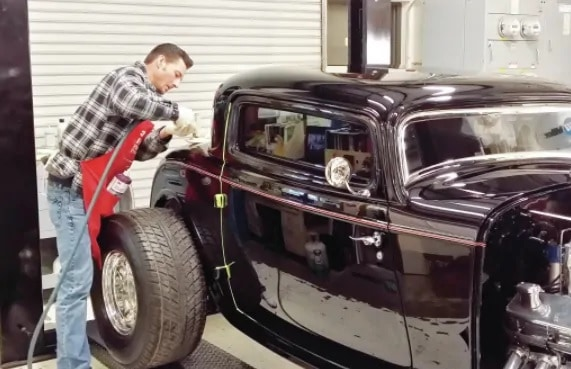 A Man Working On His Restored Hot Rod