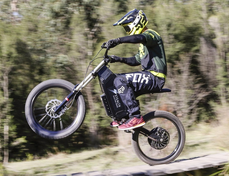 Off-road Stealth Electric Dirt Bike wheelie action shot