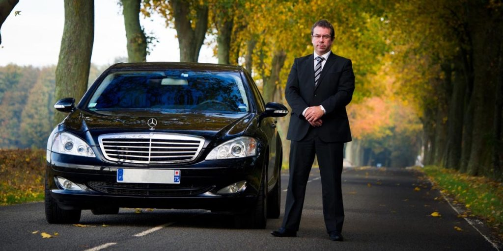 A Personal Chauffeur Standing Next To A Car