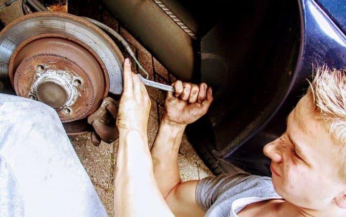 A Man Working On A Broken Car