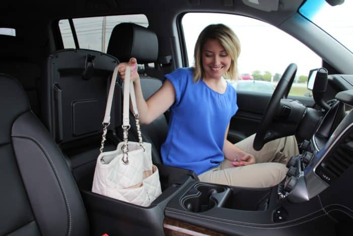 A Woman Placing A Purse Into A Compartment In Her Car