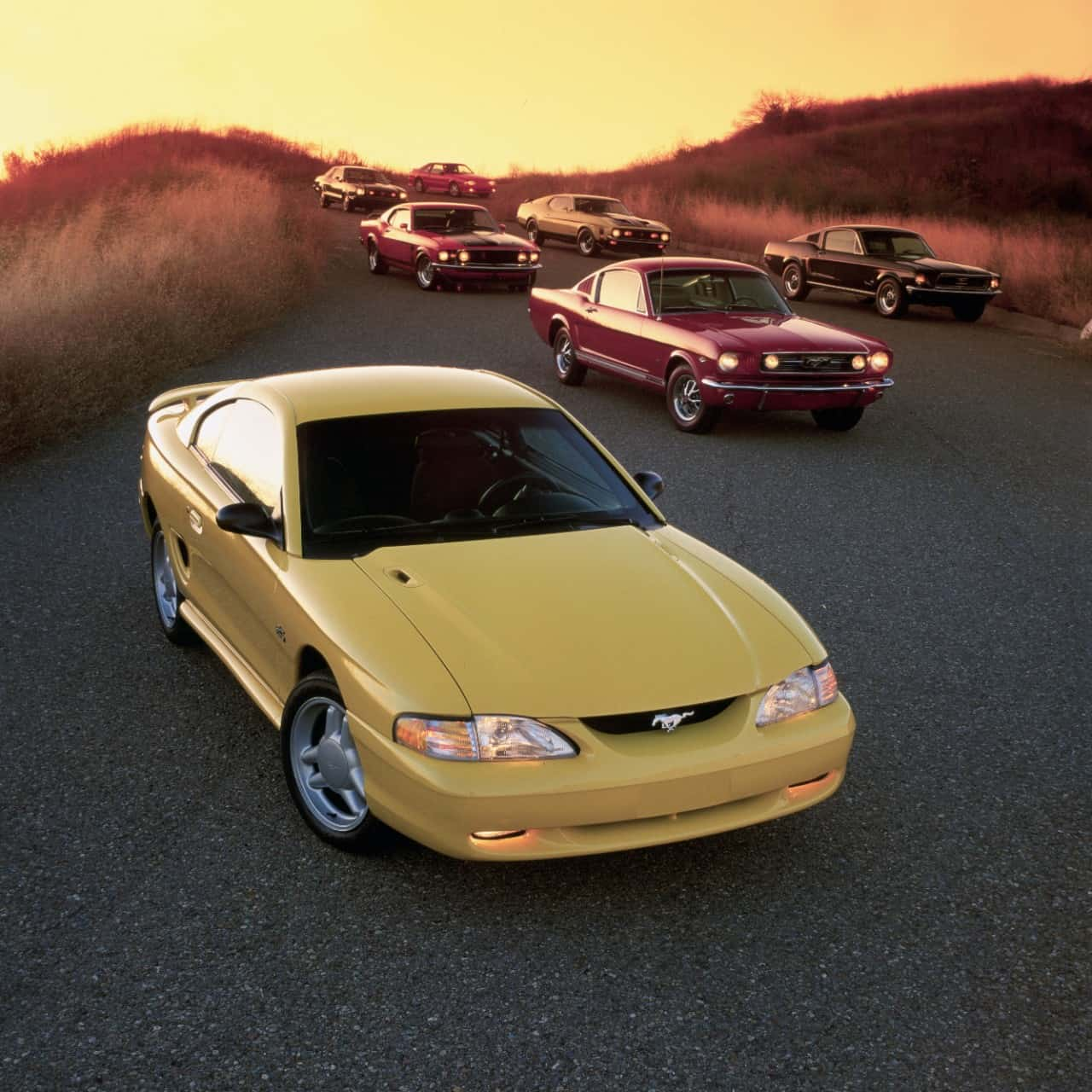 1994 Ford Mustang Coupe at sunset with every previous generation Mustang in the background