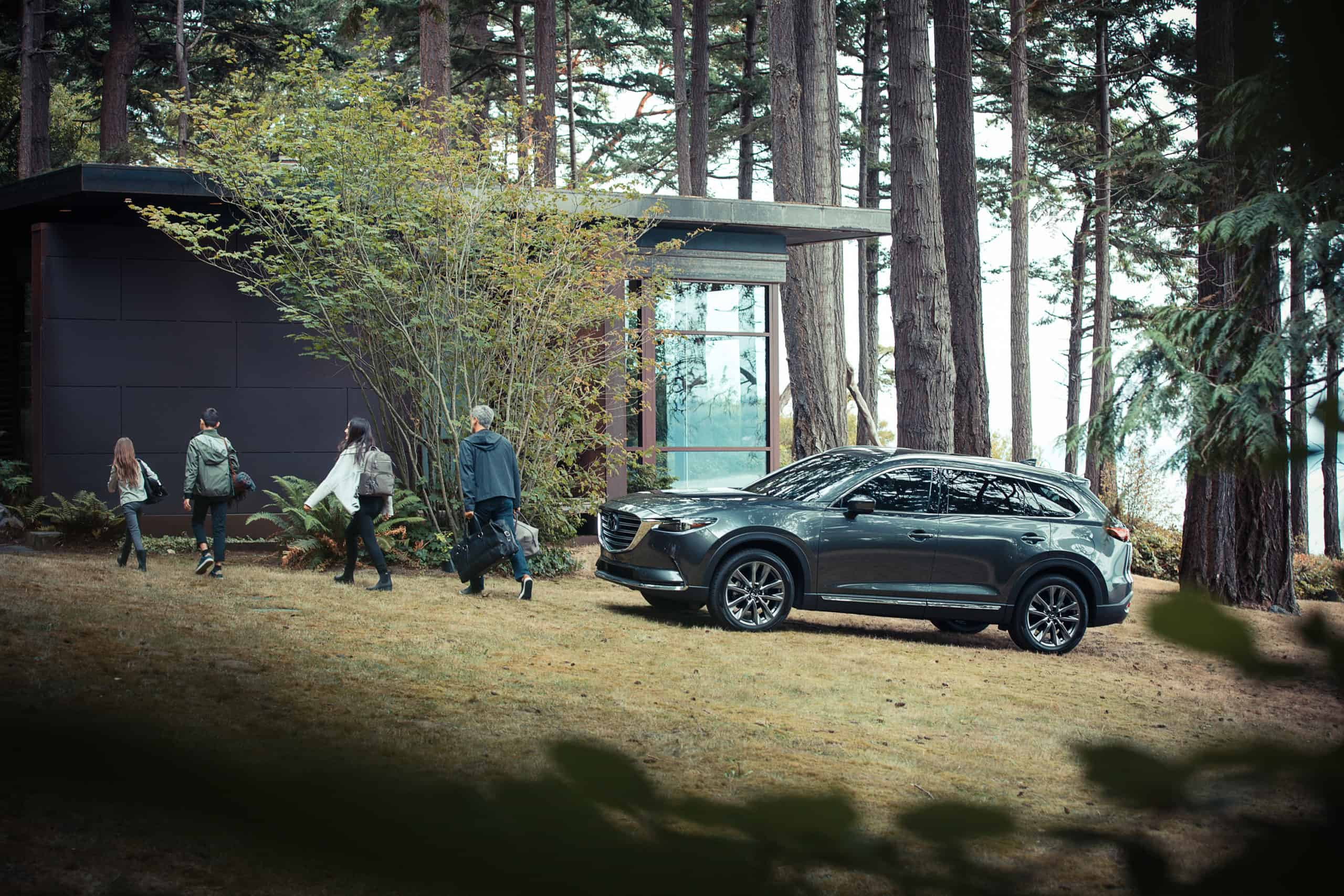 family walking into fancy cabin in the woods from mazda SUV