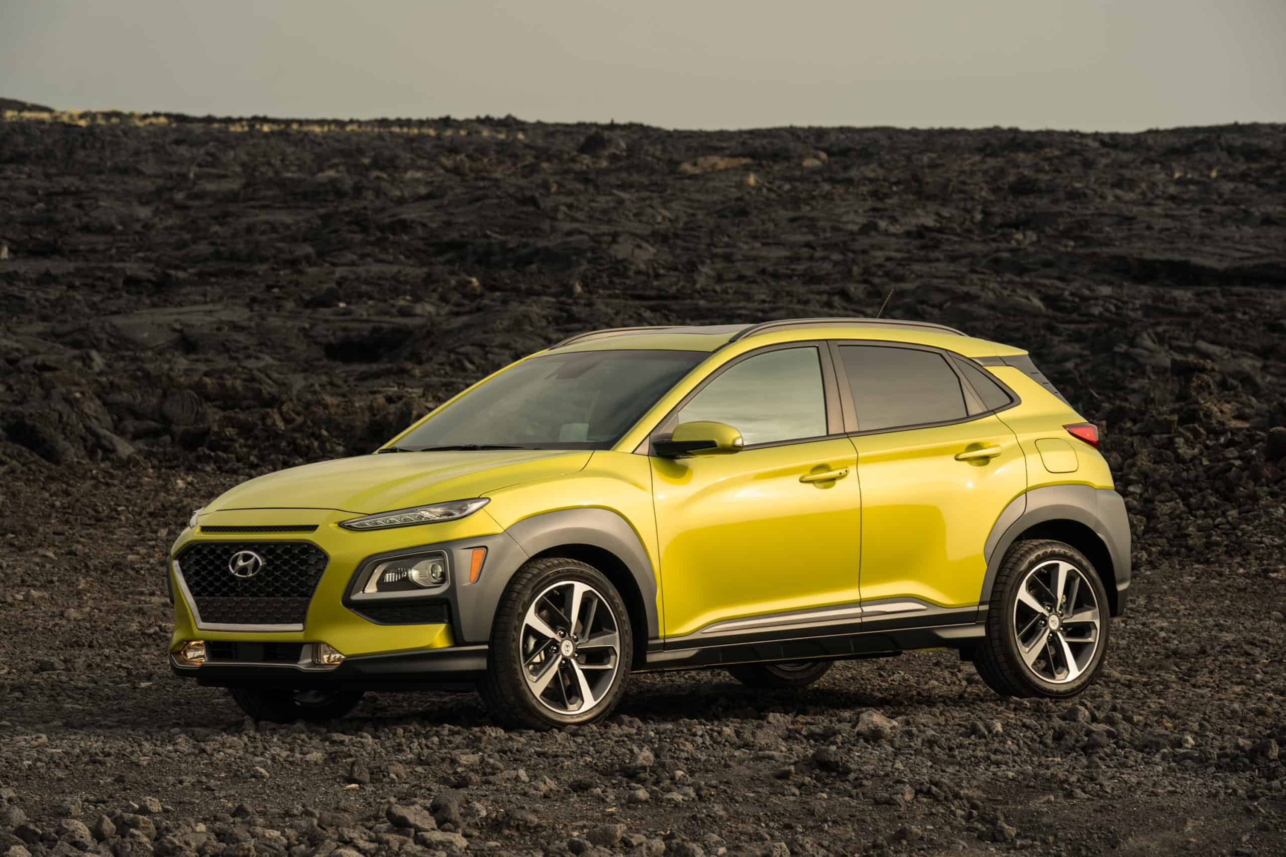 bright green Hyundai Kona in black rocks