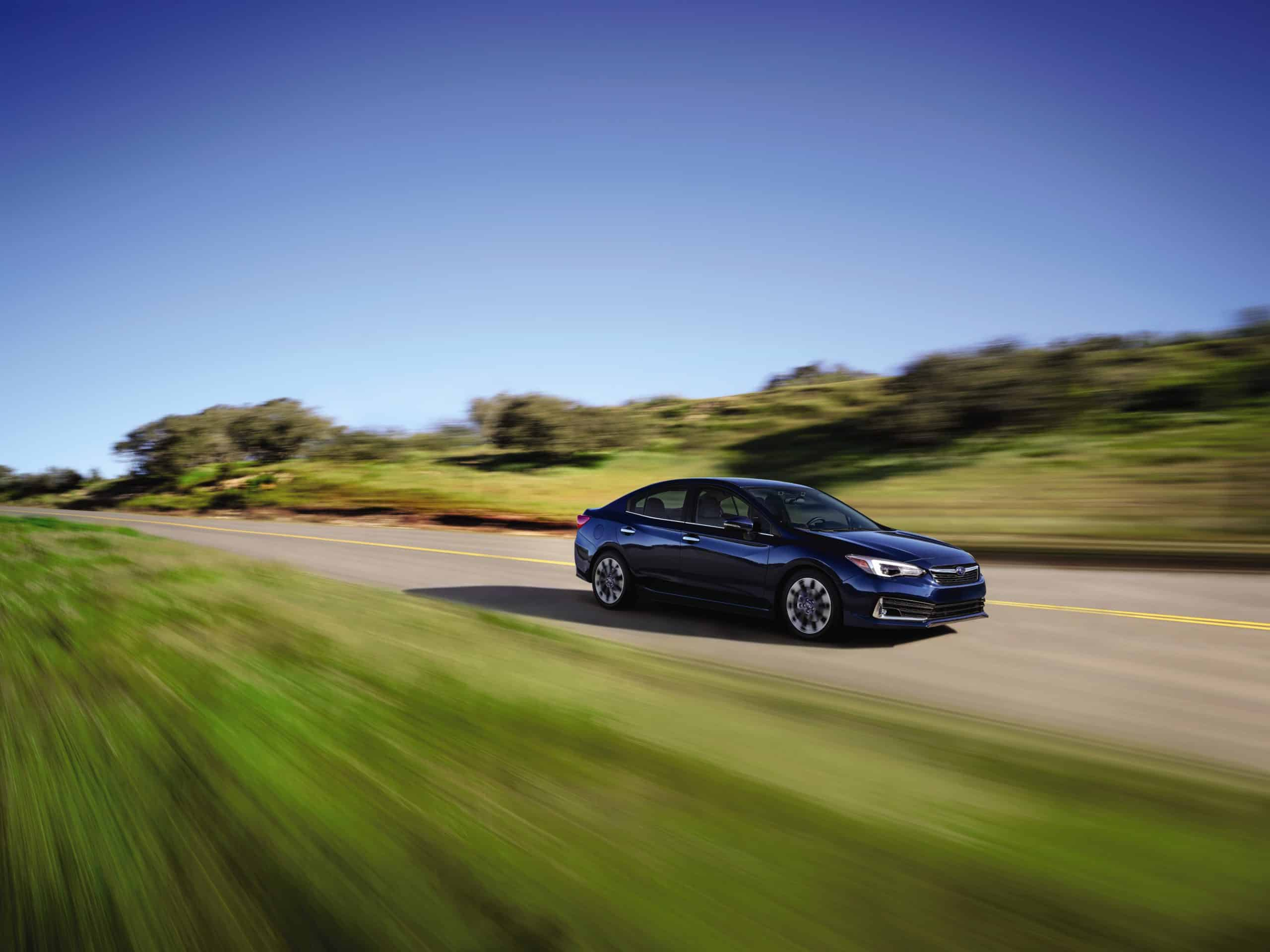 blue subaru sedan on roadway with speed blurred background