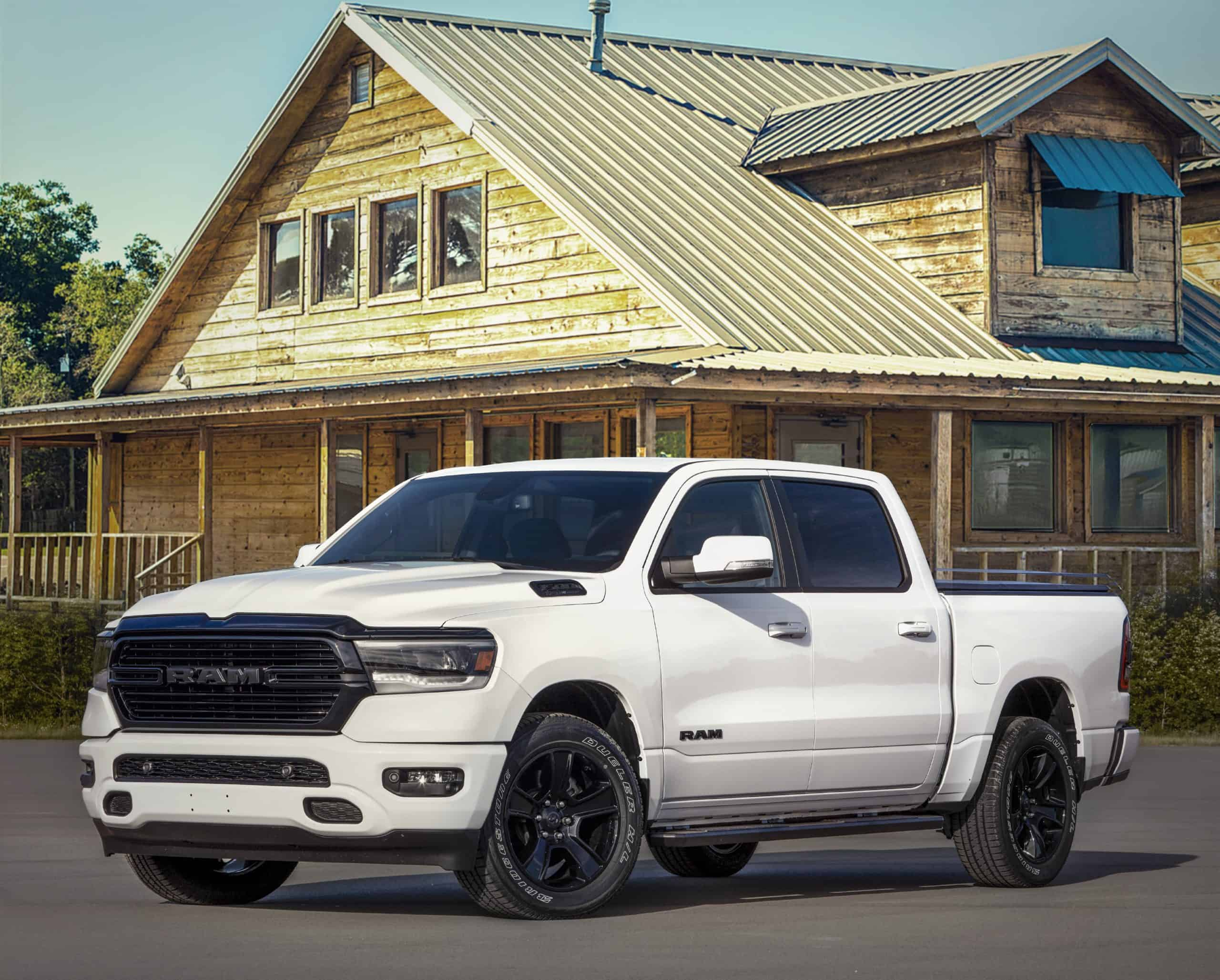 white RAM truck in front of huge wooden house